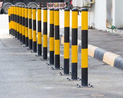 yellow and black steel bollards on street near concrete pavement